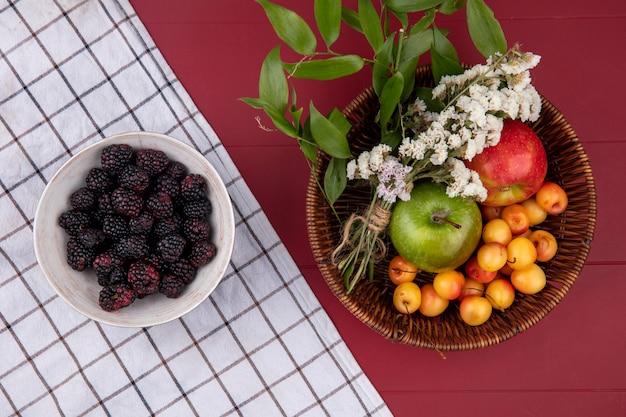 Vista dall'alto bianco ciliegia con mele colorate e fiori in un cesto e more in una ciotola su un tavolo rosso