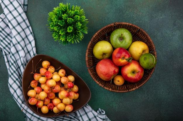 Vista dall'alto bianco ciliegia in una ciotola con le mele in un cesto su un tavolo verde