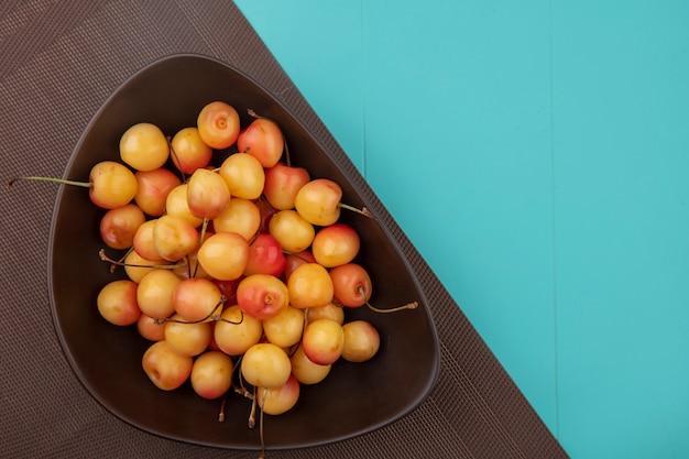 Vista dall'alto bianco ciliegia in una ciotola su un asciugamano marrone su un tavolo turchese