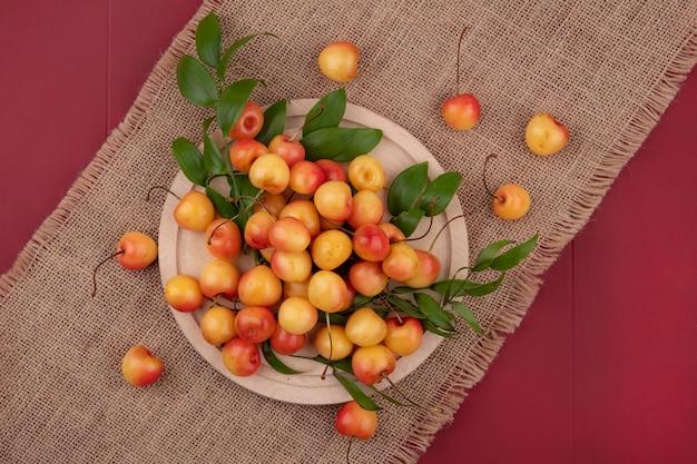 Vista dall'alto bianco ciliegia su un supporto su un tovagliolo beige su un tavolo rosso