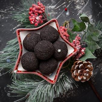 Vista dall'alto biscotti al cioccolato con pigna e foglie di abete rosso