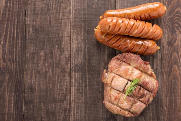 Vista dall'alto bistecca alla griglia e salsiccia su uno sfondo di legno