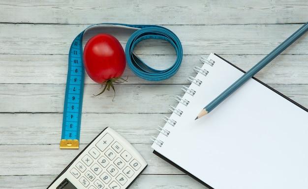 Vista dall'alto, blocco note e pomodoro succoso con nastro di misurazione, concetto di dimagrimento e mangiare sano.