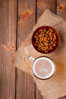 Vista dall'alto boccale di birra con mandrino duro nella ciotola a destra con spazio di copia sul tavolo di legno