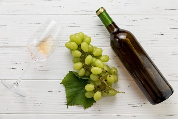 Vista dall'alto bottiglia di vino con vetro e grappolo d'uva