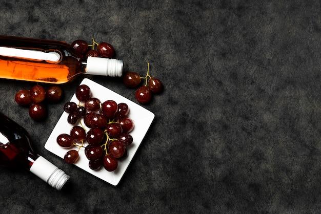 Vista dall'alto bottiglie di vino con uva