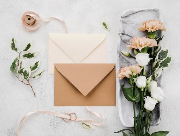 Vista dall'alto buste di invito di nozze con fiori