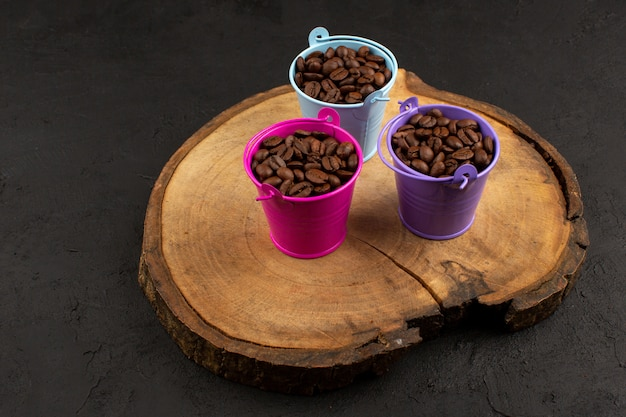 Vista dall'alto caffè marrone semi all'interno di vasi multicolori sul pavimento scuro