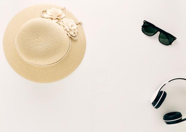 Vista dall'alto cappelli di paglia con occhiali e cuffie musicali