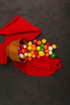 Vista dall'alto caramelle multicolori buonissimo sul tessuto rosso sul buio