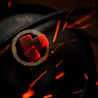 Vista dall'alto carboni ardenti con gocce di fuoco in pallone d'acciaio