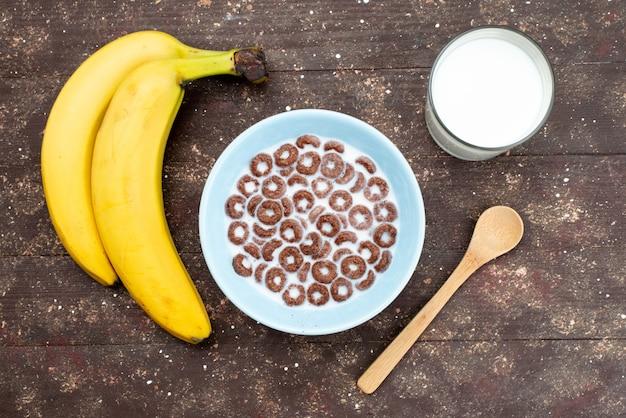 Vista dall'alto cereali al cioccolato con latte all'interno del piatto blu e insieme a banane su marrone