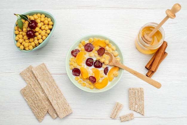 Vista dall'alto cereali con latte all'interno della piastra con cracker e miele su bianco, bere latte e prodotti lattiero-caseari
