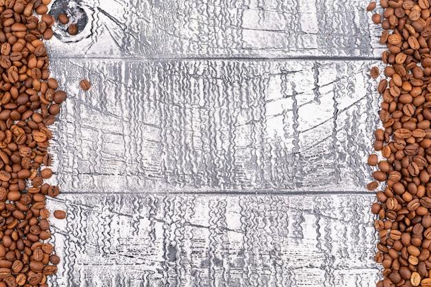 Vista dall'alto chicchi di caffè tostati sulla superficie del legno bianco