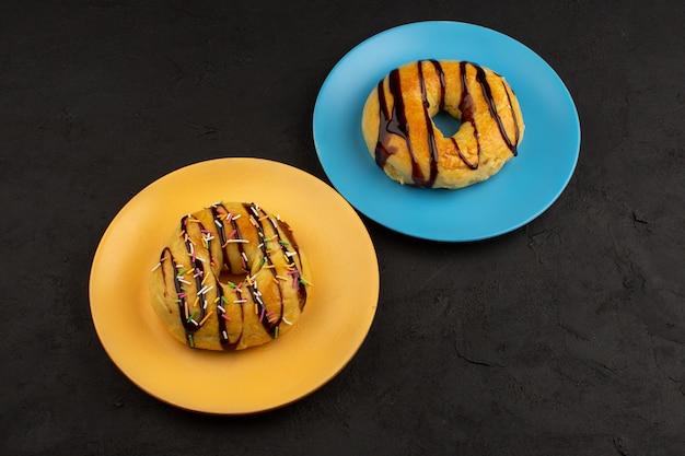 Vista dall'alto ciambelle al cioccolato all'interno di piatti colorati al buio