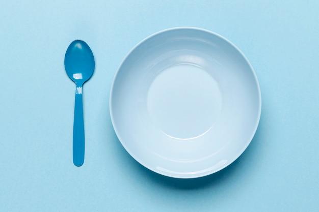 Vista dall'alto ciotola blu vuota e cucchiaio