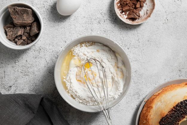 Vista dall'alto ciotola con uova e farina sul tavolo