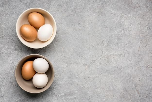Vista dall'alto ciotole con uova di gallina