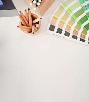 Vista dall'alto colori la matita e il piatto colorato sullo scrittorio creativo con lo spazio della copia.