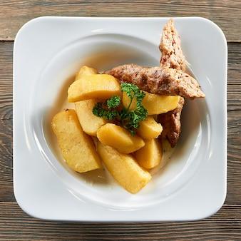 Vista dall'alto colpo di patate arrosto e salsiccia di pollo su un piatto servito al ristorante carne cibo nutrizione grassi calorie mangiare menu ordine gourmet porzione di servizio.