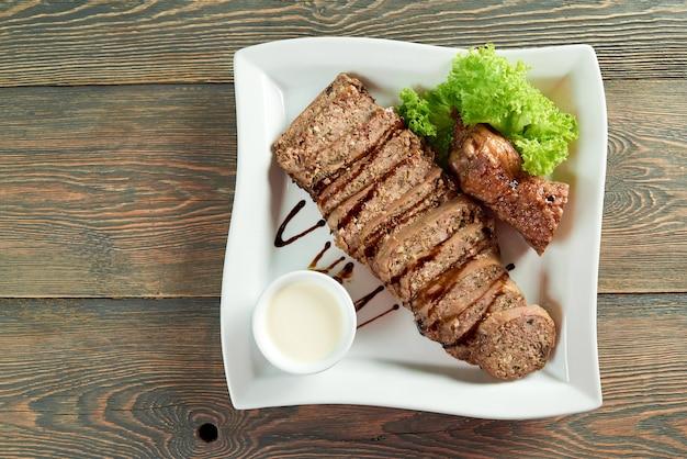 Vista dall'alto colpo orizzontale di carne a fette su un piatto quadrato bianco sul copyspace tavolo in legno mangiare cibo ricetta cena pasto pranzo cena arrosto salsa verdi decorati.