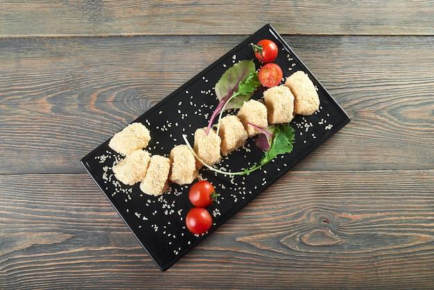Vista dall'alto colpo orizzontale di un palte nero con deliziosi involtini di formaggio con sezam servito con pomodorini e alcune foglie di tavolo in legno verde