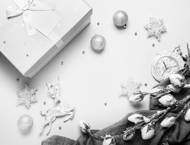 Vista dall'alto composizione di natale o capodanno su uno sfondo grigio e bianco con decorazioni natalizie bianche e argento, cervi, fiocchi di neve, palline e orologio