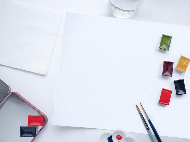 Vista dall'alto con pennelli da pittura, colori ad acquerello e foglio di carta bianco