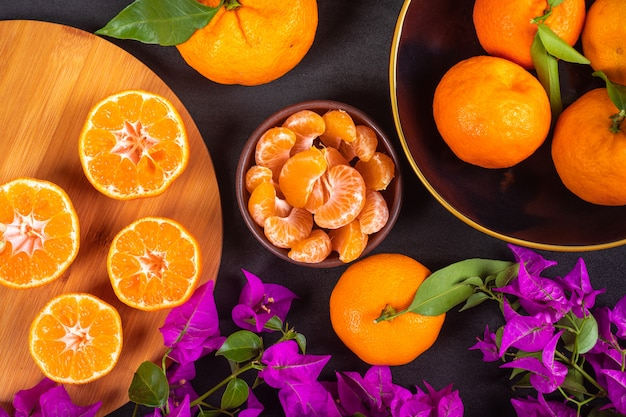 Vista dall'alto concetto di mandarino mandarini freschi e fiori viola