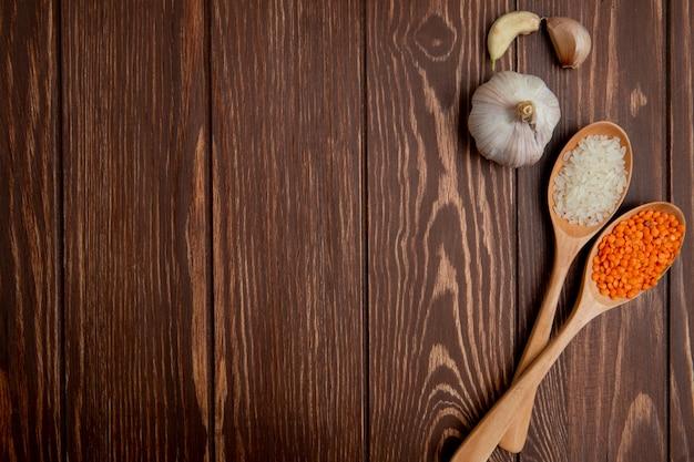 Vista dall'alto copia spazio aglio con un cucchiaio di lenticchie e riso su uno sfondo di legno