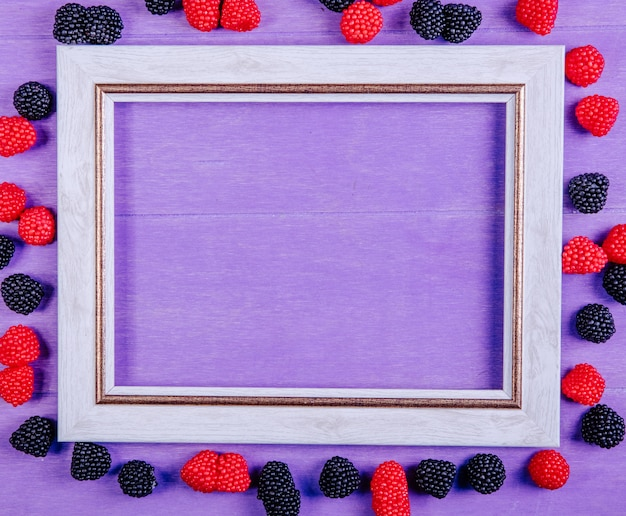 Vista dall'alto copia spazio cornice grigia con marmellate in forma di lamponi e more su uno sfondo viola