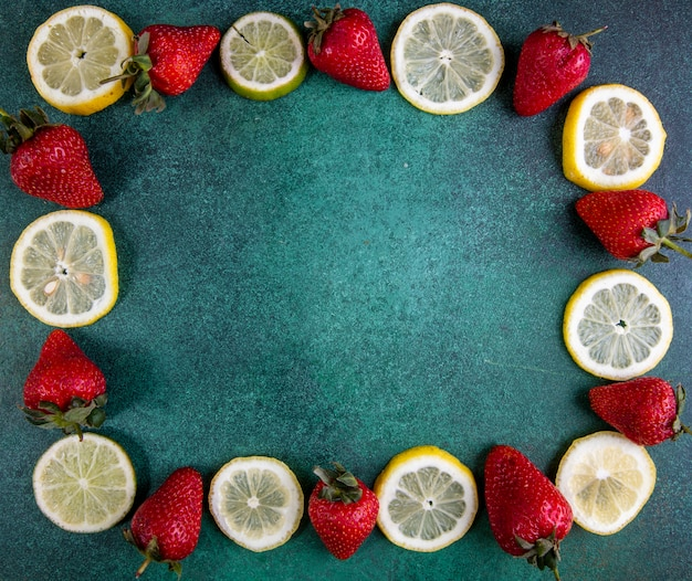Vista dall'alto copia spazio fette fette di limone e lime con fragole su verde