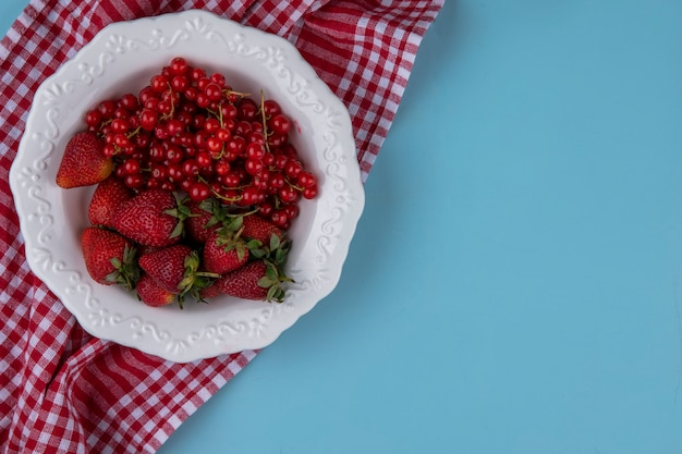 Vista dall'alto copia spazio fragole con ribes su un piatto con un asciugamano da cucina rosso su sfondo azzurro