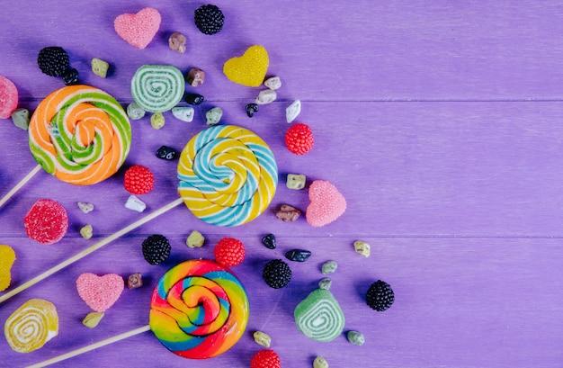 Vista dall'alto copia spazio ghiaccioli colorati con marmellata colorata di varie forme e pietre di cioccolato su uno sfondo viola