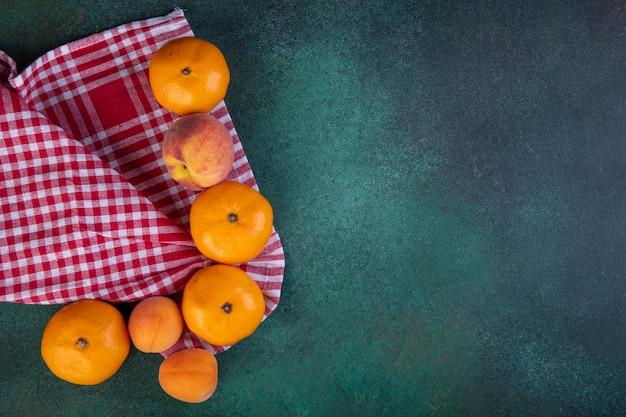 Vista dall'alto copia spazio mandarini con pesca e albicocche sul tovagliolo a scacchi rosso su verde