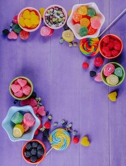 Vista dall'alto copia spazio marmellata multicolore con pietre di cioccolato e ghiaccioli colorati in piattini per marmellata su uno sfondo viola