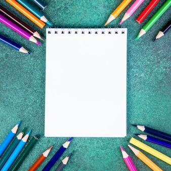 Vista dall'alto copia spazio matite colorate con blocco note su uno sfondo verde