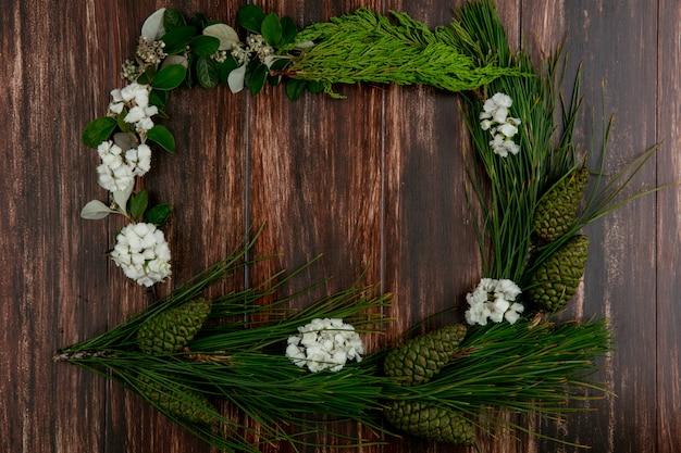 Vista dall'alto copia spazio ramo di abete con coni con fiori bianchi attorno ai bordi su un fondo di legno
