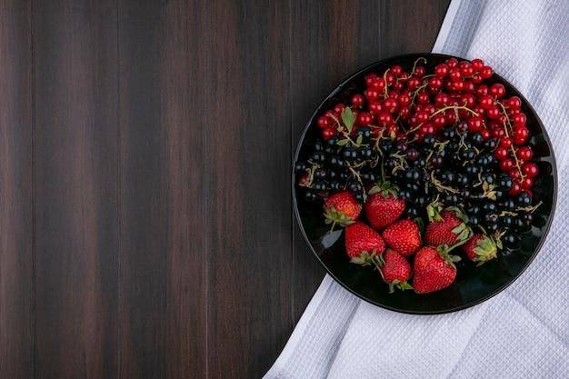 Vista dall'alto copia spazio ribes rosso e nero con fragole su un piatto su uno sfondo di legno