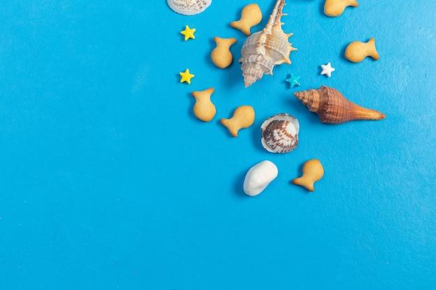 Vista dall'alto cracker a forma di pesce salati con conchiglie di mare e caramelle su sfondo blu