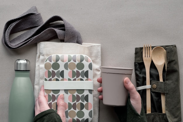 Vista dall'alto creativa, concetto di pranzo al sacco zero rifiuti, scatola da pranzo da asporto con posate in bambù, scatola riutilizzabile, sacchetto di cotone e mano con tazza da caffè. stile di vita sostenibile, piatto su carta artigianale.