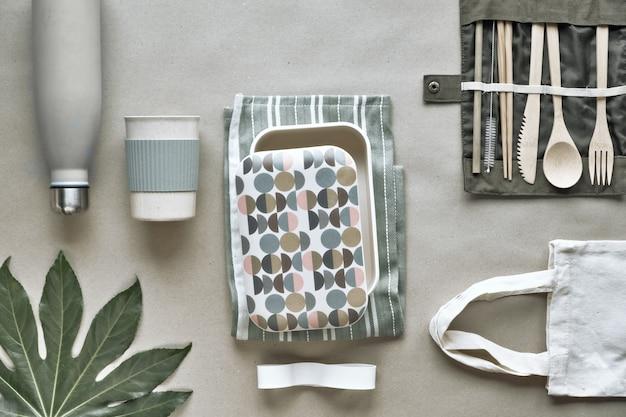 Vista dall'alto creativa, kit per il pranzo al sacco a zero rifiuti, scatola per il pranzo da asporto su sacchetto di cotone, organizzatore di posate in bambù, scatola per il pranzo in bambù e tazza riutilizzabile. stile di vita sostenibile, layout piatto su carta artigianale.