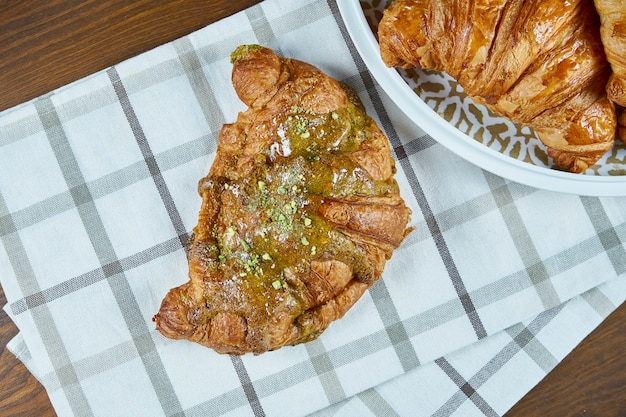 Vista dall'alto croissant appena sfornati con chokolate e pistacchi su tessuto beige su un tavolo di legno. fotografia di cibo per caffè da forno. vista da vicino.