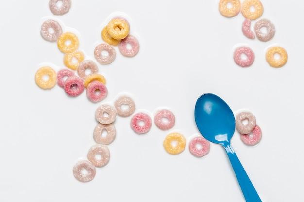 Vista dall'alto cucchiaio blu e anelli di frutta a base di cereali