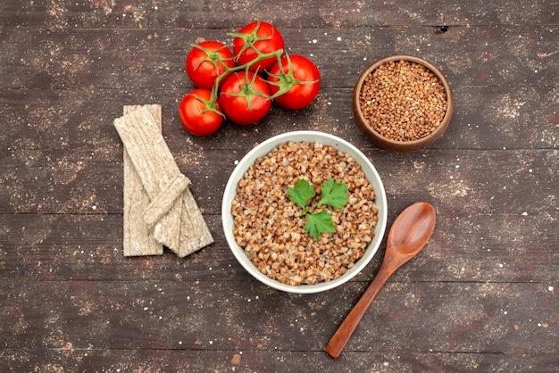Vista dall'alto cucinato gustoso grano saraceno all'interno del piatto con patatine e pomodori rossi sul buio