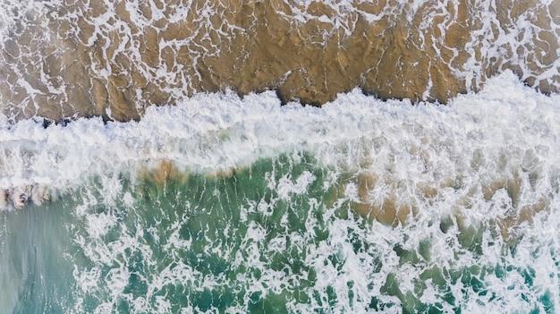 Vista dall'alto dal cielo delle onde del mare e il paesaggio della spiaggia di sabbia.