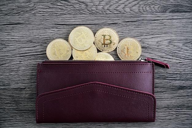 Vista dall'alto dei bitcoin dorati sul portafoglio in pelle rossa