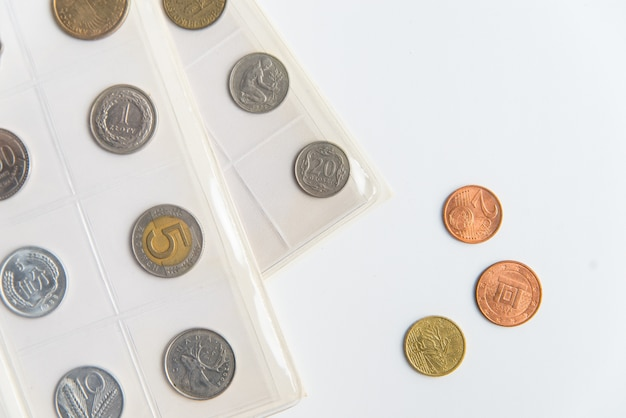 Vista dall'alto dei fogli e delle monete numismatiche dell'album. collezione di monete rare su sfondo bianco con spazio di copia