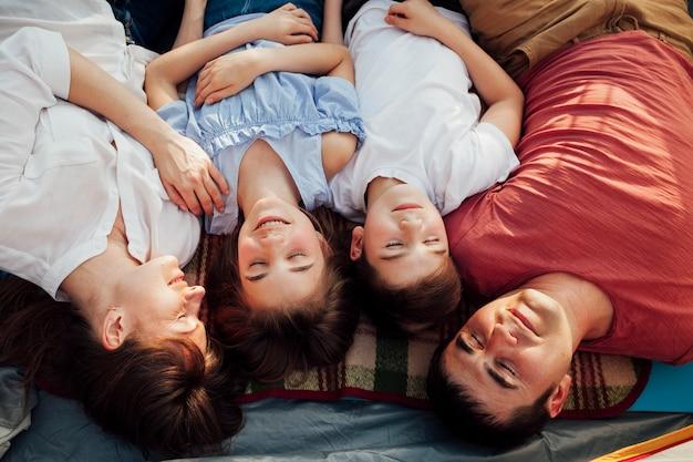 Vista dall'alto dei genitori con i loro bambini che riposano in tenda