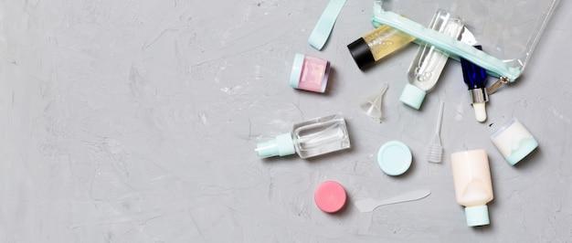 Vista dall'alto dei mezzi per la cura del viso: bottiglie e vasetti di tonico, acqua detergente micellare, panna, dischetti di cotone su sfondo grigio.